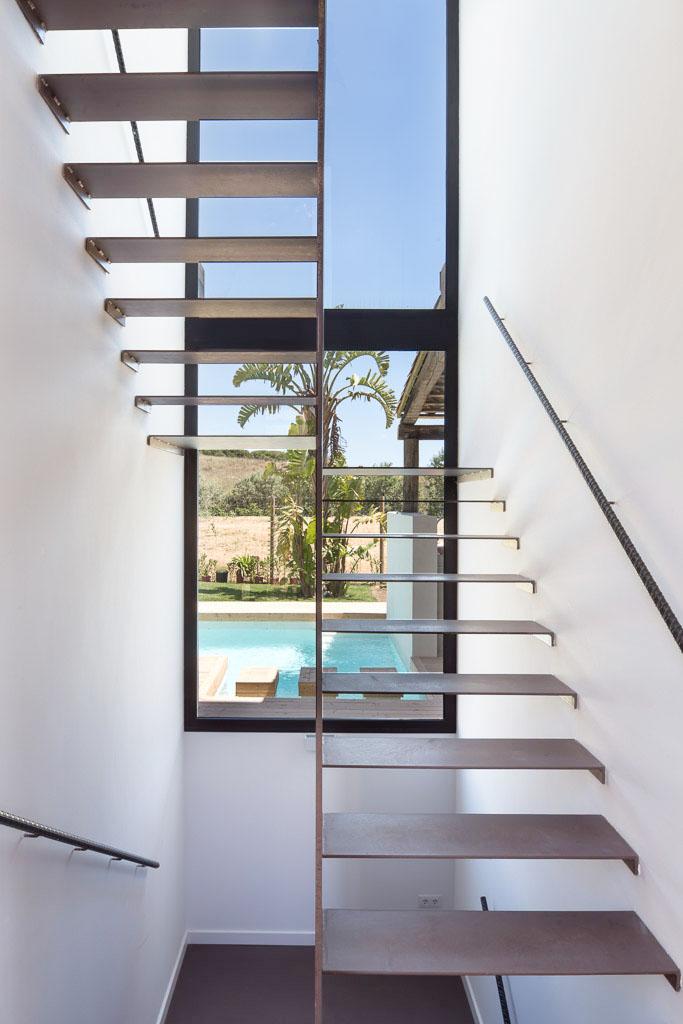 Escalera de metal con vistas a la piscina y jardín - Casa A | 08023 Arquitectos